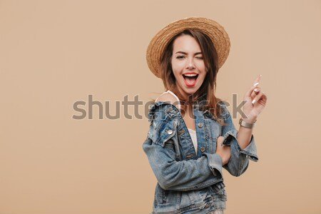 Amazed young pretty girl in checkered shirt showing thumb up ges Stock photo © deandrobot