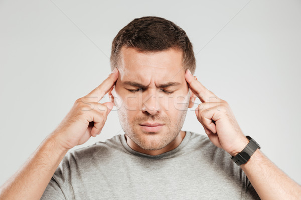 Man with headache. Eyes closed. Stock photo © deandrobot