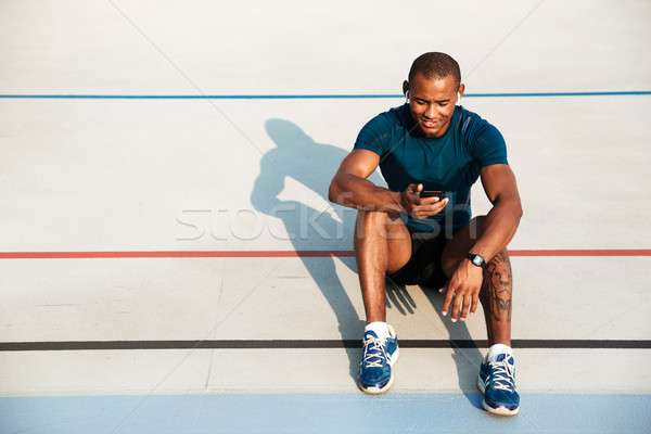 Portrait of a smiling young african fitness man in earphones Stock photo © deandrobot