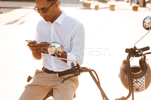 Young african man in sunglasses sitting on modern motorbike outdoors Stock photo © deandrobot