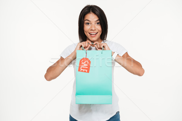 Portrait of an excited young woman holding sale shopping bag Stock photo © deandrobot