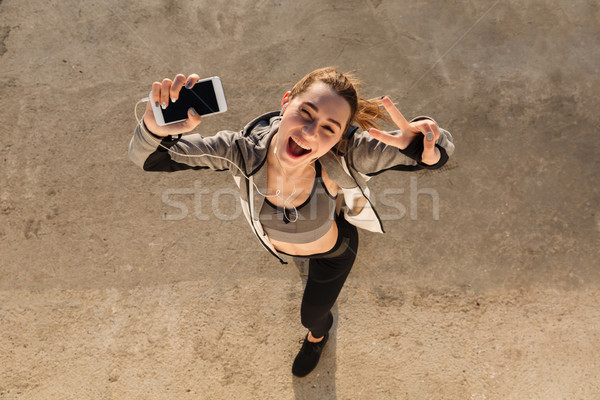 Top view of funny brunette sport woman showing peace sign while  Stock photo © deandrobot