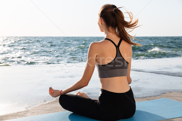 Portrait of young healthy woman sitting in lotos pose while prac Stock photo © deandrobot