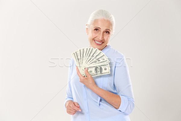 Beautiful smiling elderly lady holding fan of money, looking at  Stock photo © deandrobot