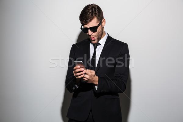 Közelkép fotó meglepett szakállas férfi fekete öltöny Stock fotó © deandrobot