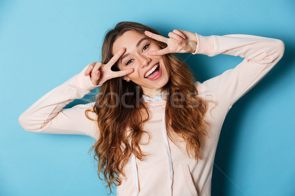 Cute funny young cheerful woman showing peace gesture. Stock photo © deandrobot