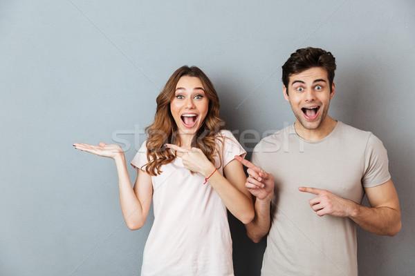 Portrait excité satisfait couple permanent pointant Photo stock © deandrobot