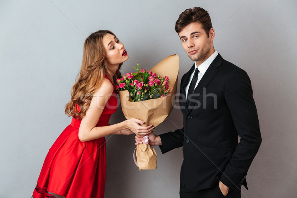 Portrait of a young man giving his girlfriend flower bouquet Stock photo © deandrobot