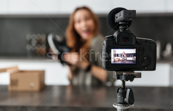 Cheerful young girl recording her video blog episode Stock photo © deandrobot