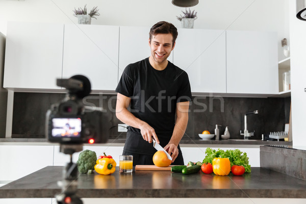 Cheery young man filming his video blog episode Stock photo © deandrobot