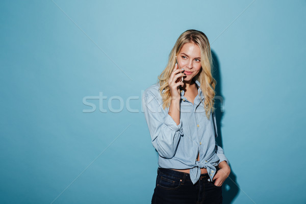 Pretty blonde woman in shirt talking by smartphone Stock photo © deandrobot