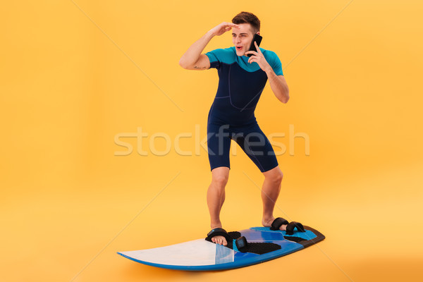 Image of Happy surfer in wetsuit using surfboard Stock photo © deandrobot