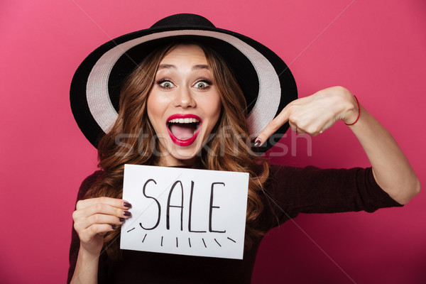 Happy lady wearing hat pointing holding sale text. Stock photo © deandrobot