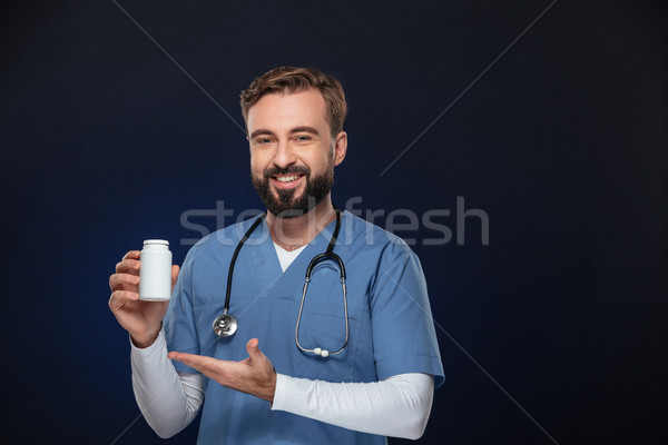 Portrait of a happy male doctor dressed in uniform Stock photo © deandrobot