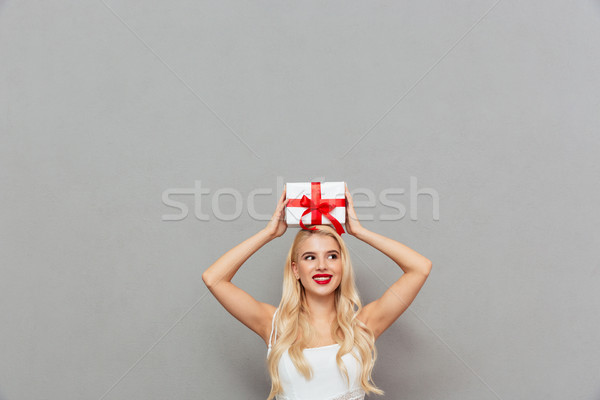 Portrait of a pretty woman holding gift box on head Stock photo © deandrobot