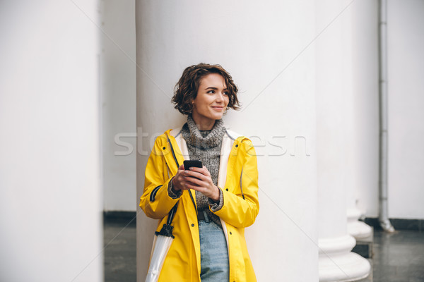 Amazing young woman dressed in raincoat. Stock photo © deandrobot