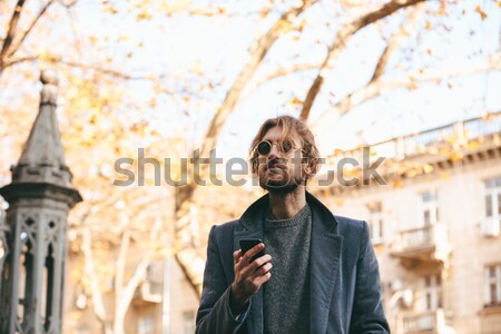 Portrait of content female 20s holding modern gadget receive tex Stock photo © deandrobot