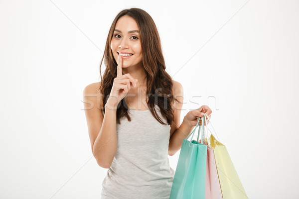 Picture of flirting woman holding shopping packs and asking keep Stock photo © deandrobot