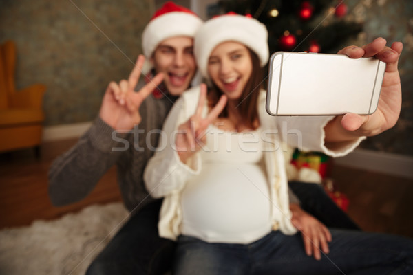 Smiling cheery pregnant woman with her husband celebrating christmas while sitting together on a flo Stock photo © deandrobot