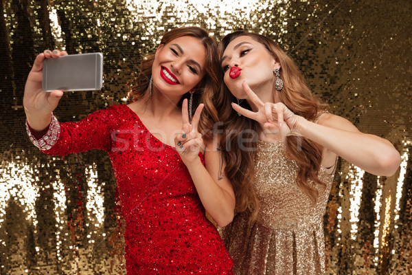 Portrait of two funny happy women in sparkly dresses Stock photo © deandrobot