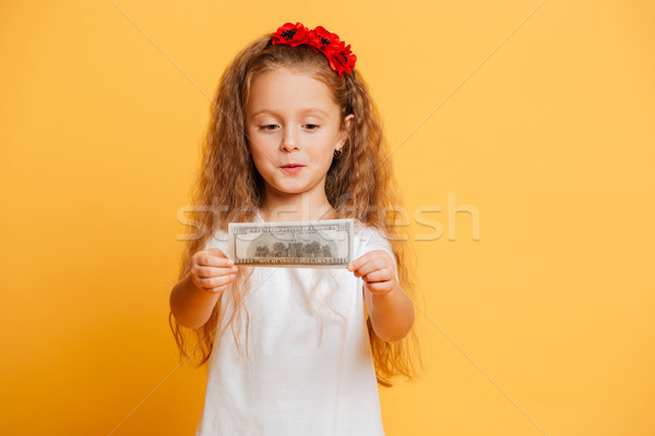 Little cute girl holding money looking aside. Stock photo © deandrobot
