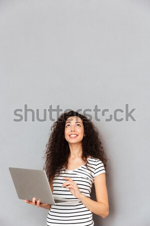 Happy lady with curly hair typing message or communicating in in Stock photo © deandrobot