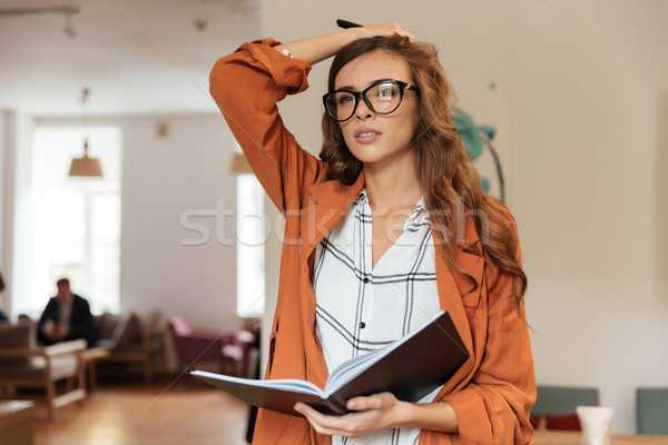 Portrait of a confident woman making notes Stock photo © deandrobot
