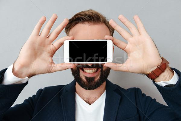 Młodych brodaty człowiek okładka twarz smartphone Zdjęcia stock © deandrobot
