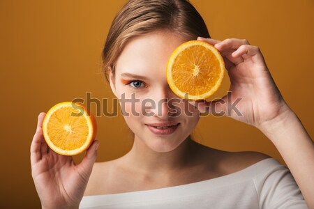 Attractive half-naked woman holding orange slices near her face Stock photo © deandrobot