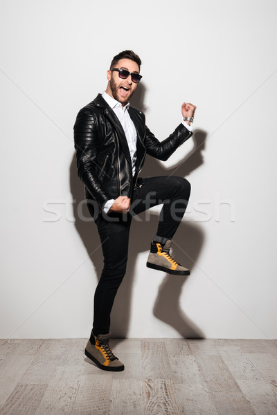 Full length portrait of a cheery happy man Stock photo © deandrobot