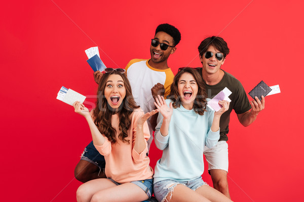 Group of happy excited friends holding passport and flying tickets Stock photo © deandrobot