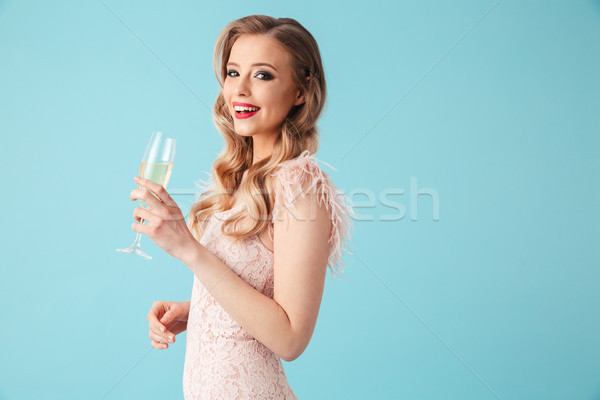 Side view of Smiling blonde woman in dress drinking champange Stock photo © deandrobot