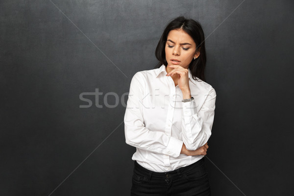 Portrait of concentrated woman 30s with long brown hair wearing  Stock photo © deandrobot