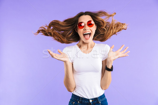 Screaming shocked woman isolated over purple wall background. Stock photo © deandrobot