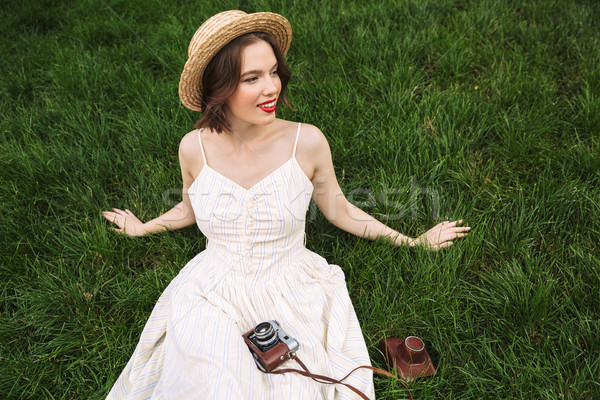 Happy woman in dress and straw hat looking away Stock photo © deandrobot