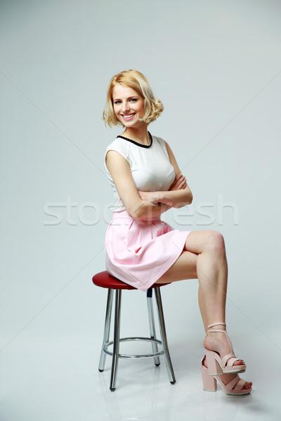 Jóvenes mujer sonriente armas doblado sesión gris Foto stock © deandrobot