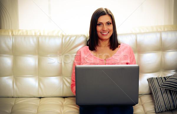Sorrindo sessão sofá laptop casa Foto stock © deandrobot