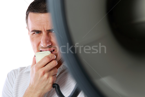 Closeup portrait of a man roaring loudly into megaphone  Stock photo © deandrobot