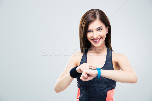 Smiling woman using activity tracker Stock photo © deandrobot