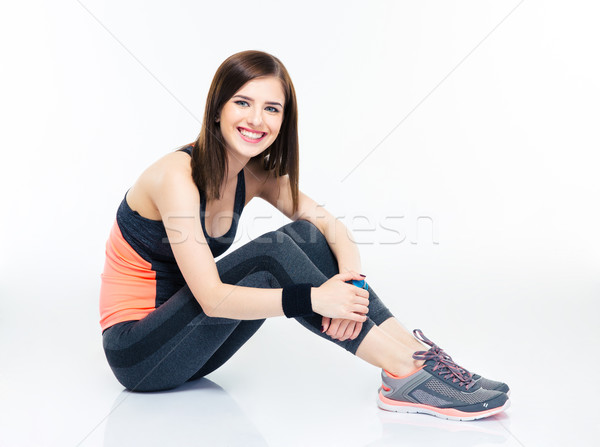 Smiling fitness woman sitting on the floor Stock photo © deandrobot