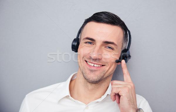 Mutlu genç erkek operatör kulaklık bakıyor Stok fotoğraf © deandrobot