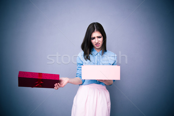 Dissatisfied woman opening gift Stock photo © deandrobot