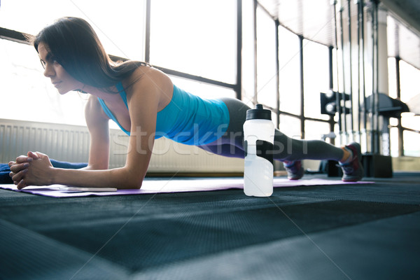 Young fit woman working out on yoga mat Stock photo © deandrobot