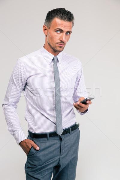 Handsome businessman using smartphone Stock photo © deandrobot