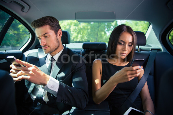 Businessman and businesswoman using smartphone in car Stock photo © deandrobot