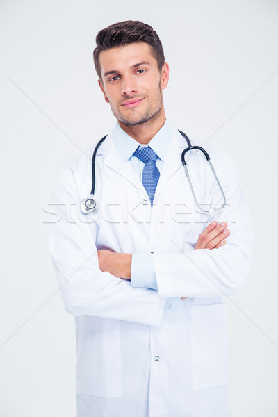 Male doctor standing with arms folded Stock photo © deandrobot