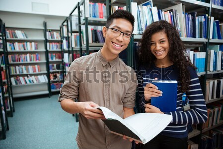 Stock photo: Happy students searching book in library