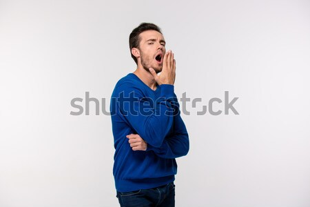 Portrait of a young man yawning  Stock photo © deandrobot