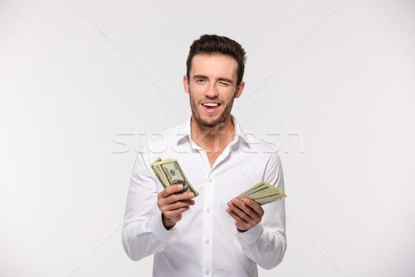Férfi tart dollár bankjegyek kacsintás portré boldog Stock fotó © deandrobot