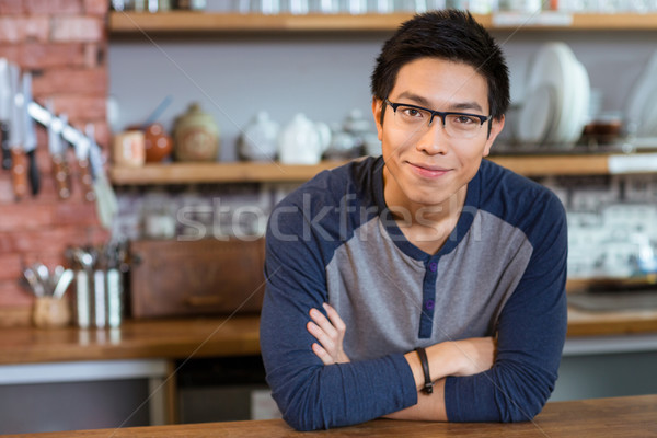Confident handsome man standing in cafe with arms crossed Stock photo © deandrobot